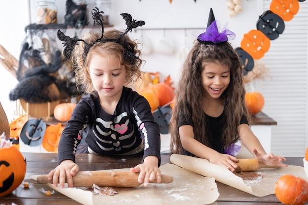 Duas crianças com fantasia de bruxa fazendo biscoitos e se divertindo na cozinha, comemorando o dia das bruxas
