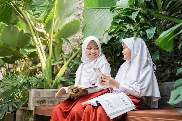 Duas crianças com lenço na cabeça em uniformes escolares, usando um smartphone e um livro enquanto conversam ...