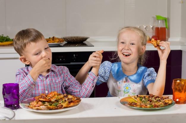 Duas crianças comemorando comendo pizza