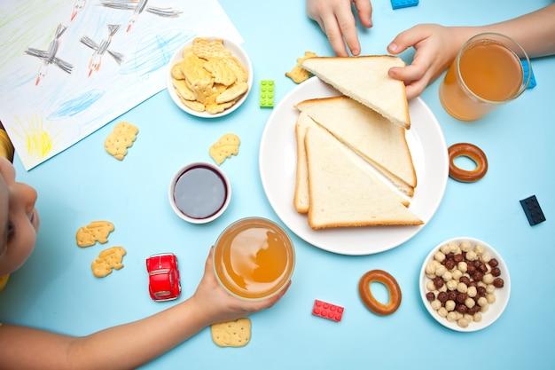 Duas crianças comendo lanches, sanduíches e biscoitos