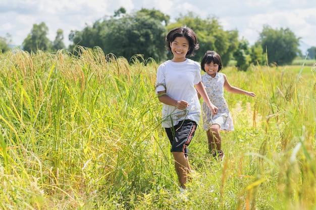 Duas crianças correndo nos arrozais. jogando divertido no horário de verão