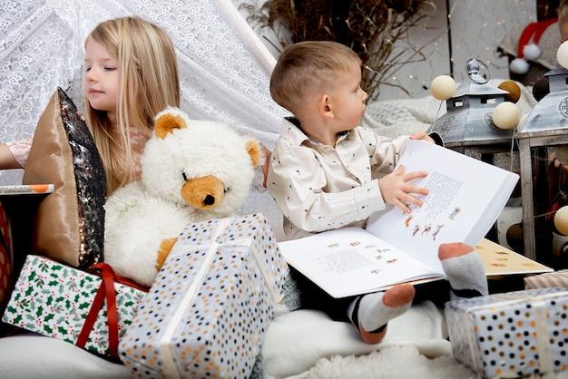 Duas crianças crianças lêem um livro entre caixas de presente de natal em uma casa decorada. feliz natal e boas festas!