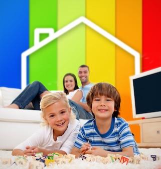Duas crianças deitado em um tapete em frente à ilustração da casa e linhas de eficiência energética
