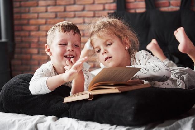 Duas crianças deitam-se em uma cama grande e leem um livro interessante. eles estão vestidos com os mesmos pijamas
