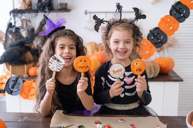 Duas crianças diversas com a fantasia de bruxa se divertindo na cozinha, comendo biscoitos, comemorando o dia das bruxas