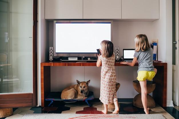 Duas crianças do sexo feminino assistindo muito perto de televisão e computador