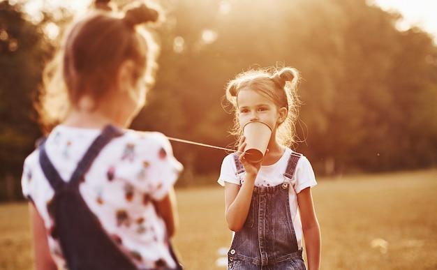 Duas crianças do sexo feminino em pé no campo e falando usando um barbante podem telefonar.