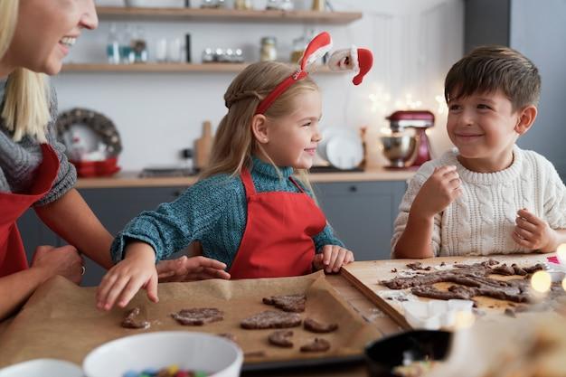 Duas crianças e a mãe cortando biscoitos de gengibre