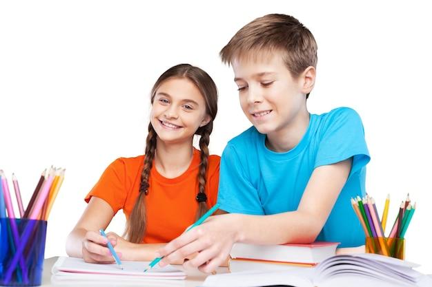 Duas crianças em idade escolar com cofrinho e livros didáticos usando materiais de arte