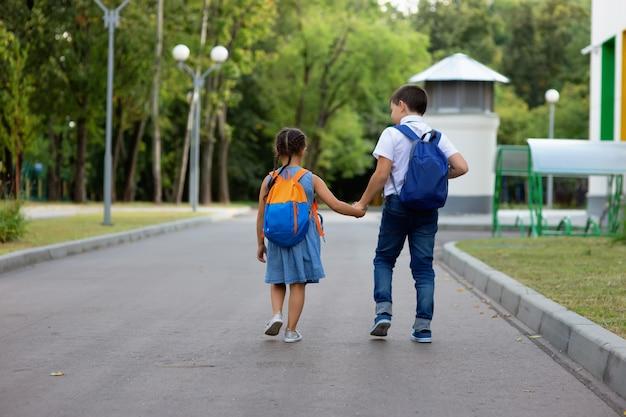 Duas crianças em idade escolar, uma menina e um menino, com mochilas de mãos dadas, correm para a rua verde.