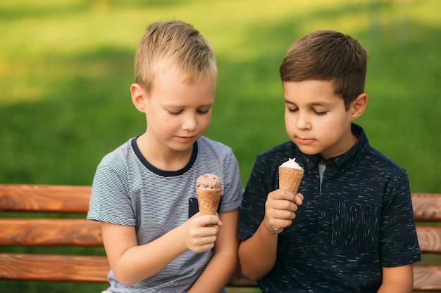 Duas crianças estão brincando no parque. dois lindos meninos de camiseta e shorts se divertem sorrindo