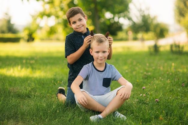 Duas crianças estão brincando no parque. dois lindos meninos em camisetas e shorts se divertem sorrindo. eles comem sorvete, pulam, correm. o verão é ensolarado.