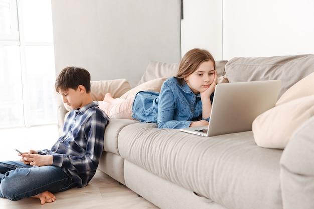 Duas crianças europeias modernas, menino e menina, descansando no sofá em casa, enquanto usam o telefone celular e o laptop