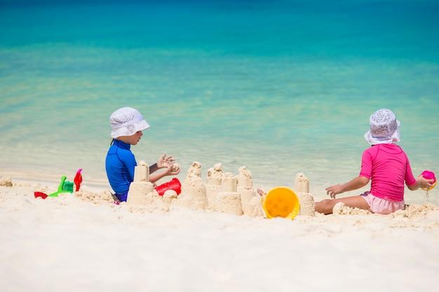 Duas crianças fazendo castelo de areia e jogando na praia tropical