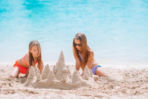 Duas crianças fazendo castelo de areia e se divertindo na praia tropical