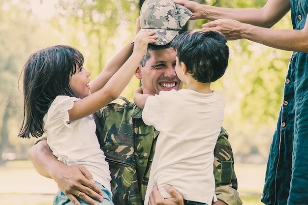 Duas crianças felizes e a mãe se encontrando e abraçando um pai militar em uniforme de camuflagem ao ar livre