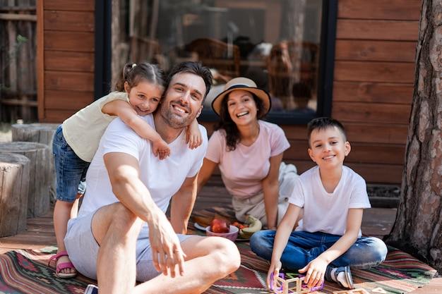 Duas crianças felizes e seus pais, relaxando no quintal perto de uma casa de campo, passam as férias juntos, aproveitam o calor do verão
