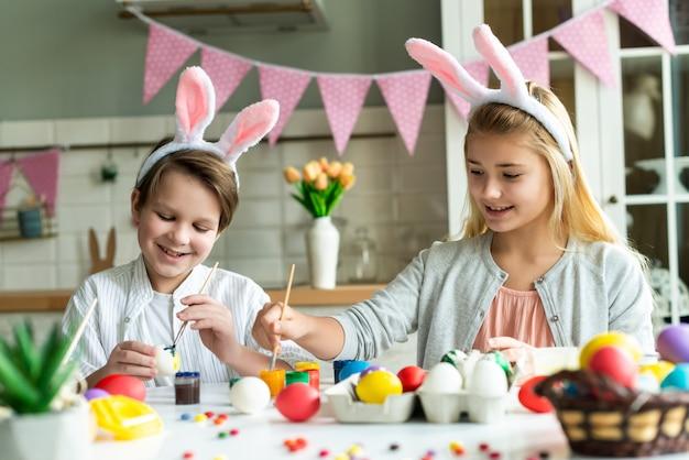 Duas crianças felizes em orelhas de coelho pintam ovos de páscoa na mesa.