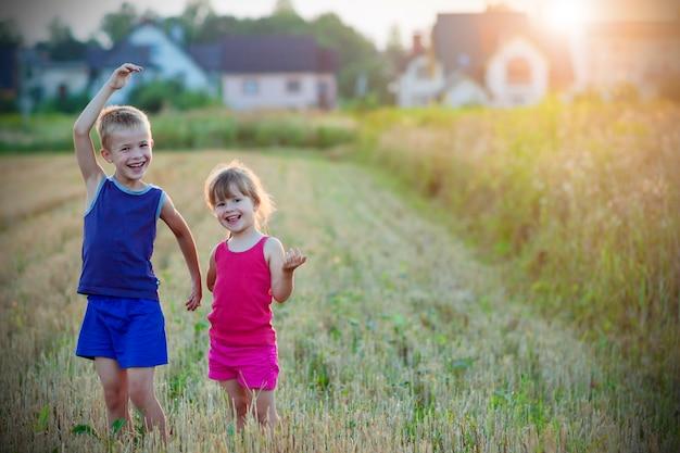 Duas crianças felizes em pé no campo de trigo.