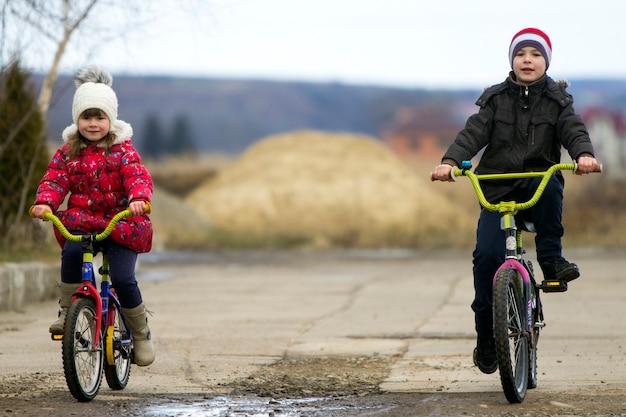 Duas crianças felizes, menino e menina, andando de bicicleta ao ar livre em tempo frio