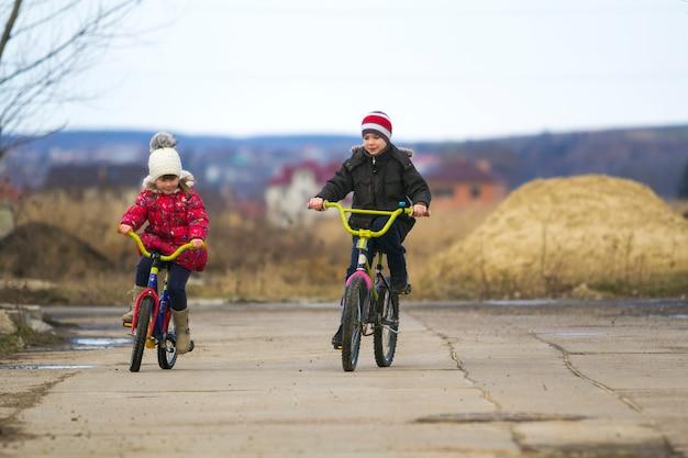 Duas crianças felizes menino e menina, andar de bicicleta ao ar livre em tempo frio