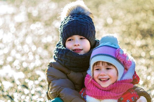 Duas crianças felizes, menino e menina, ao ar livre em um dia ensolarado de inverno
