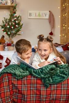 Duas crianças fofas e felizes escrevendo uma carta para o papai noel