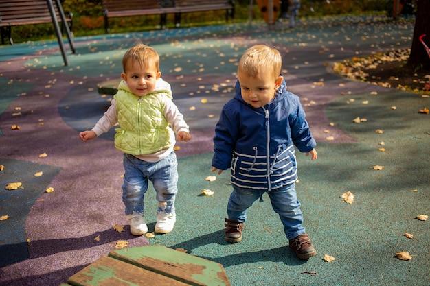 Duas crianças fofas, menino e menina, caminham juntos no parque de outono, amizade desde a infância.
