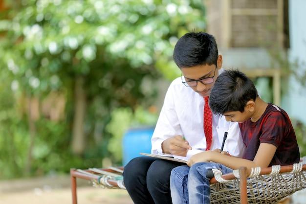 Duas crianças indianas estudando em casa