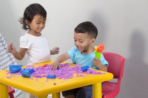 Duas crianças jogam areia em casa