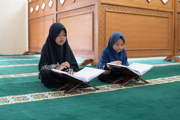 Duas crianças lêem o alcorão sagrado