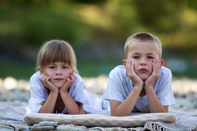 Duas crianças loiras bonitos felizes jovens, menino e menina, irmão e irmã, deitado na praia de seixos no fundo desfocado brilhante dia ensolarado de verão. amizade de irmãos, lazer e conceito de férias perfeitas.