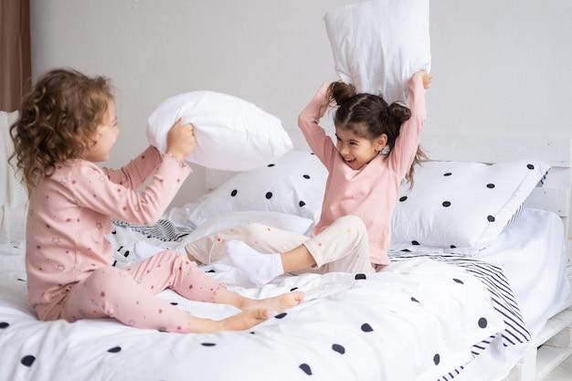 Duas crianças meninas de pijama brigando de travesseiros na cama em um apartamento moderno e bem iluminado