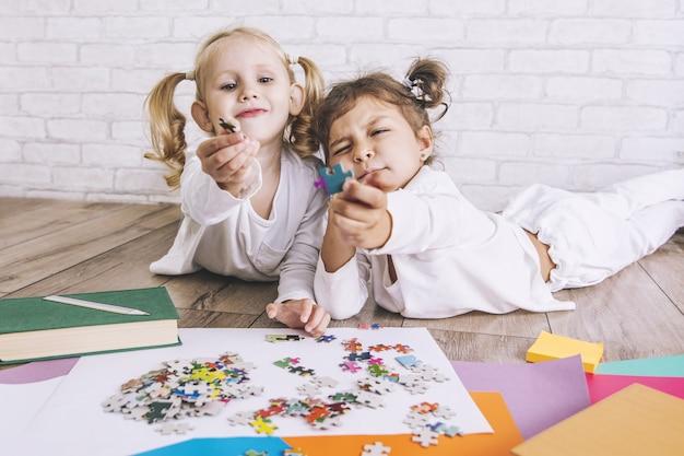 Duas crianças, meninas em idade pré-escolar montam o quebra-cabeça no chão