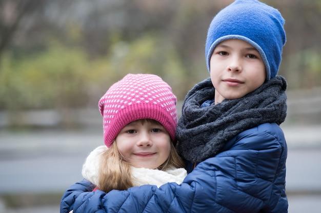 Duas crianças menino e menina, abraçando-se ao ar livre, vestindo roupas quentes no outono frio ou inverno.
