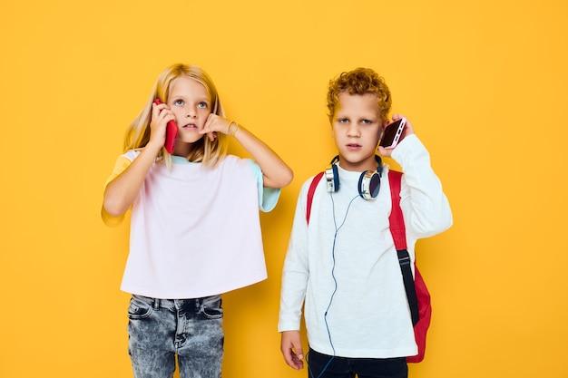 Duas crianças, menino e menina, com mochilas escolares, telefone, entretenimento, comunicação