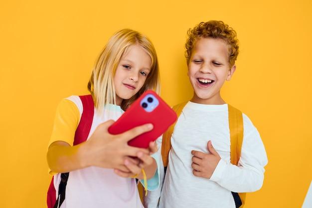 Duas crianças, menino e menina, conversando e sorrindo, emoções, alegria, fundo amarelo
