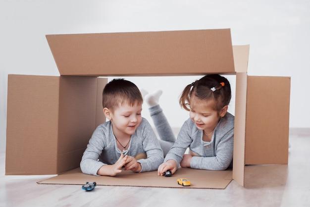 Duas crianças menino e menina jogando carros pequenos em caixas de papelão. foto. as crianças se divertem. foto do conceito. as crianças se divertem