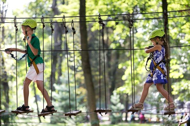 Duas crianças, menino e menina no cinto de proteção e capacetes de segurança na atividade de escalada no caminho da corda.