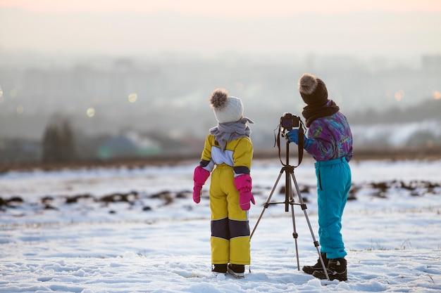 Duas crianças menino e menina se divertindo lá fora no inverno, brincando com a câmera fotográfica em um tripé no campo coberto de neve.