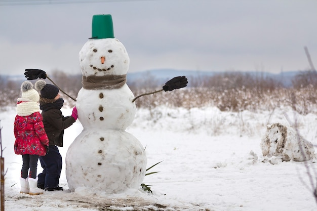 Duas crianças, menino e menina, terminam de fazer boneco de neve sorridente com chapéu balde, lenço e luvas na paisagem de campo de inverno vazio e fundo de espaço de cópia de céu azul. feliz natal feliz ano novo.