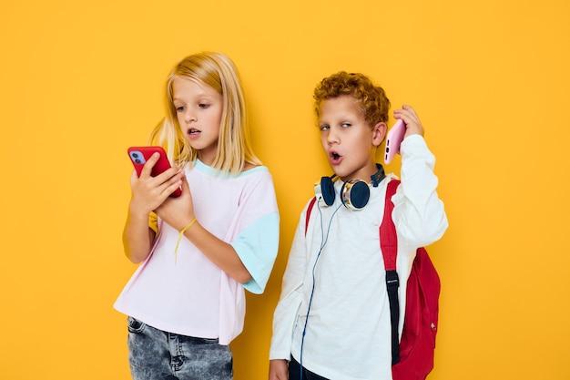 Duas crianças, menino e menina, usam gadgets com fones de ouvido, concerto do vício de crianças e gadgets