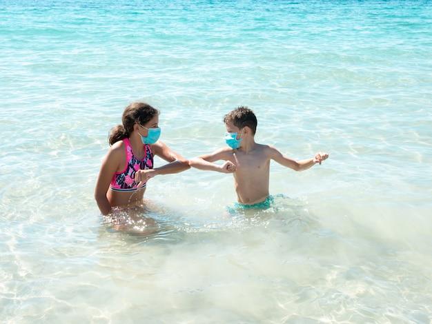 Duas crianças na praia vestindo máscaras protetoras e saudação com os cotovelos