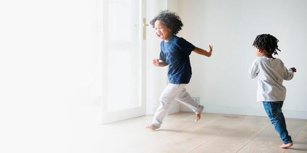 Duas crianças negras brincando e se perseguindo em um espaço vazio de uma sala vazia