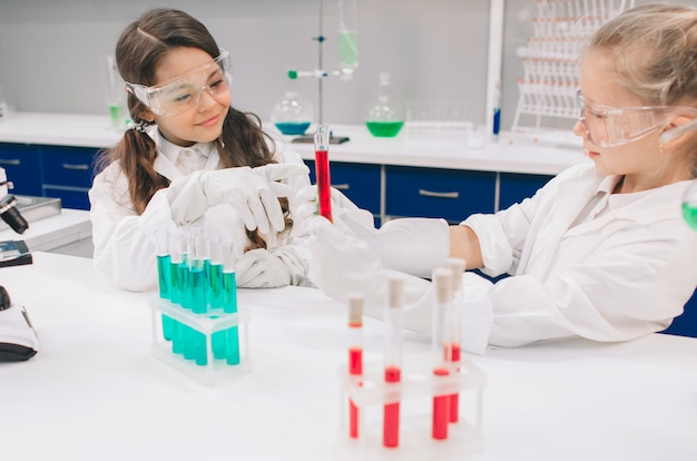 Duas crianças no jaleco aprendendo química no laboratório da escola. jovens cientistas em óculos de proteção fazendo experimento em laboratório ou gabinete de químico. estudando ingredientes para experimentos.