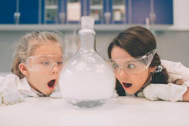Duas crianças no jaleco aprendendo química no laboratório da escola. jovens cientistas em óculos de proteção fazendo experimento em laboratório ou gabinete de químico. experimentos perigosos.