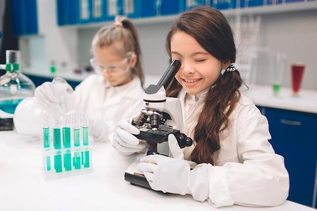 Duas crianças no jaleco aprendendo química no laboratório da escola. jovens cientistas em óculos de proteção fazendo experimento em laboratório ou gabinete de químico. olhando através do microscópio