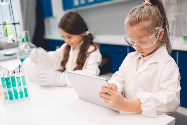 Duas crianças no jaleco aprendendo química no laboratório da escola. jovens cientistas em óculos de proteção fazendo experimento em laboratório ou gabinete de químico. trabalhando em um tablet.