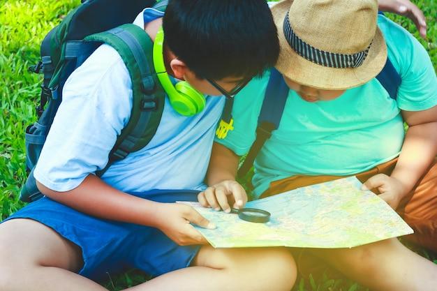 Duas crianças observando o mapa para viajar