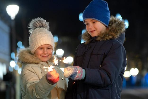 Duas crianças pequenas bonitos, menino e menina com roupas de inverno quente segurando fogos de artifício em chamas na noite escura ao ar livre bokeh. conceito de celebração de ano novo e natal.